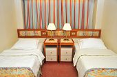 stock photo of cruise ship  - Front view of luxurious resort room with twin beds in a cruise ship cabin - JPG