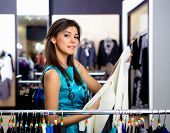image of young girls  - young girl in a shop buying clothes - JPG