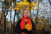Beautiful Blond Woman Standing Under Maple Tree In Autumn Park. Smiling Pretty Woman In Orange Scarf poster