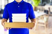 Food Delivery Service Or Order Food Online. Delivery Man In Blue Uniform With Hand Holding Food Pack poster