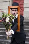 stock photo of heartwarming  - A Vintage Gent Bestows Flowers Through A Wooden Picture Frame With A Revelation Of Romance For The Most Heartwarming Presents Are Gifts From The Imagination - JPG