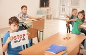 Little boy with sign Stop bullying in classroom poster