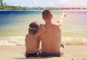 Father And Son Having Fun On Tropical White Sand Beach.back View Of Father And Son Sitting On Sand L poster