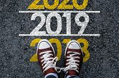 Happy New Year 2019. Man Legs In Sneakers Standing On Asphalt Road And Number 2018 Next To Number 20 poster