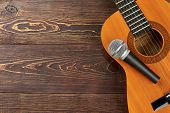 Acoustic Guitar With Microphone On Wooden Background. Classical Guitar With Microphone On Brown Wood poster