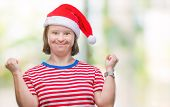 Young adult woman with down syndrome wearing christmas hat over isolated background celebrating surp poster