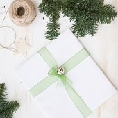 Closeup Of Christmas Gift Decorated With Ribbon And Bell. New Year Present In White Paper On White W poster