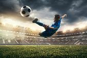 Young Boy With Soccer Ball Doing Flying Kick At Stadium. Football Soccer Players In Motion On Green  poster