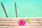 Large Pink Sun Hat And Green Beach Sandal On The Wooden Deck By The Sea poster