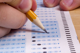 stock photo of bubble sheet  - Student filling out answers to a test with a pencil - JPG