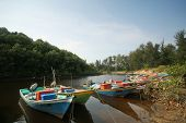 a flotilla of fishing boats line up on the river banks after returning from sea. poster