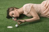 image of ladies golf  - Pretty girl with brown hair lying on grass and playing with golf ball - JPG