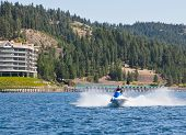 picture of waverunner  - Beautiful woman out on the lake riding a wave runner on bright sunny day - JPG