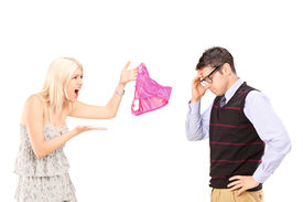 stock photo of knickers  - Angry girlfriend shouting at her boyfriend and holding female knickers isolated on white background - JPG