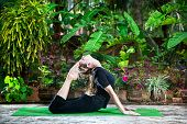 pic of raja  - Yoga Raja Kapotasana backward bending pose by woman in black cloth in the garden with palms banana trees and plants in the pots - JPG