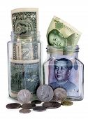 picture of zedong  - Money jars overflow with American and Chinese bank notes and coins against white background - JPG