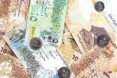 foto of dirhams  - The State of Qatar currency bills and coins scattered as a background - JPG