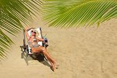 image of bimbo  - Beautiful young woman at the summer lounge under palm trees - JPG