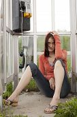 stock photo of phone-booth  - A young women sitting on the floor of a phone booth looking depressed and sad after conversation on phone - JPG