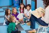 image of preschool  - Teacher reading story book to children in kindergarten - JPG