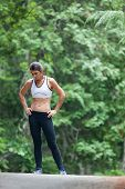 foto of main idea  - Athletic middle aged woman rests with her hands on her hips while on a run in green leaved woods on a dirt road in Surry Maine USA during the Summer.
