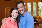 stock photo of entryway  - Caucasian wife and hispanic husband standing in entryway of home with tall wooden door and windows high ceilings smiling during day - JPG