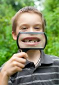 picture of tooth gap  - Young boy showing missing baby tooth through hand magnifier shallow DOF - JPG