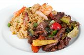stock photo of chinese food  - a meal of beef and black bean sauce served with the chefs special fried rice on a white plate - JPG