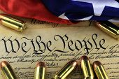 stock photo of ammo  - US Constitution Bill of Rights with 45 caliber bullets and American flag - JPG