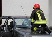 picture of firehouse  - Italian fireman while breaks the glass windshield broken car to rescue the injured persons - JPG