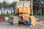 stock photo of heavy equipment operator  - positive driver of heavy equipment rests in the workplace - JPG