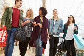 stock photo of mall  - Group Of Young Friends Shopping In Mall Together - JPG