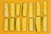 stock photo of zea  - Fresh ripe yellow corn on the cob lined up in a double row on a yellow background for healthy vegetarian and vegan cuisine overhead view - JPG