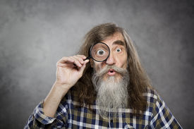 pic of investigation  - Senior old man looking through zoom magnifying glass - JPG
