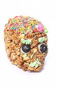 picture of day dead skull  - Closeup of honey covered cereal candy skull with sprinkles on white background in celebration of Day of the Dead - JPG