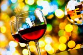 image of sparkling wine  - two red wine glasses against colorful bokeh lights and sparkling disco ball background festive and fun concept  - JPG
