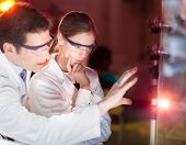 foto of laser beam  - Portrait of a focused electrical engineering researchers in their working environment checking the phenomenon of breaking laser beam on the glass surface - JPG