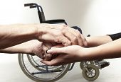 stock photo of wheelchair  - Hands of an elderly man holding the hand of a younger woman on wheelchair background - JPG