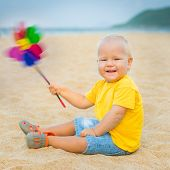 pic of laughable  - Baby playing with toy windmill - JPG