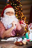 stock photo of ball cap  - Senior man in Santa cap and beard painting toy ball and looking at camera - JPG