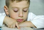 stock photo of storytime  - young boy reading a book - JPG