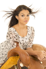 picture of western saddle  - a woman with her hair blowing laying on a western saddle - JPG