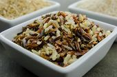 picture of ceramic bowl  - Wild rice in a ceramic bowl in the foreground before brown and white rice  - JPG