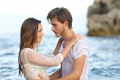 picture of bathing  - Profile of a young couple in love looking each other ready to kiss bathing in the sea - JPG