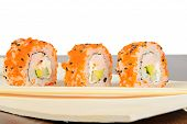 foto of masago  - Closeup California maki sushi with masago on the wooden plate - JPG
