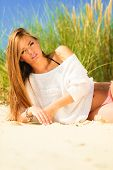 foto of dune grass  - Young woman female model posing outdoor on background of dunes sky and grass