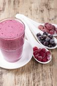 picture of smoothies  - Smoothies from the berries of black and red currants gooseberries and yogurt in a glass on a wooden brown table - JPG