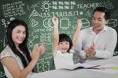 picture of applause  - Portrait of happy little girl raise hands after finish her homework and get applause - JPG