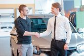 stock photo of showrooms  - Done deal. Male customer shaking hands with a young smiling sales consultant in showroom with a new car and showroom view on the background in blurry
