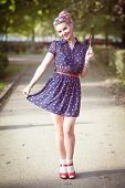 picture of fifties  - Beautiful young woman in fifties style with braces holding candy outdoor - JPG